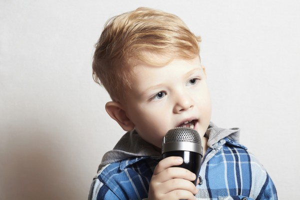 Поет в микрофон